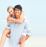 Happy young man piggybacking his girlfriend Stock Images