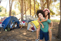 Happy young man piggybacking woman with friends in background Stock Images