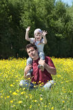 Happy young man play with little daughter among yellow flowers Stock Photos