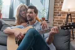 Happy young man playing guitar for girlfriend. At home royalty free stock photography