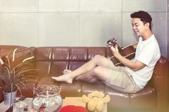 Happy young man playing the guitar in living room stock images