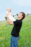 Happy young man playing his baby boy on nature Stock Images