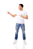 Happy young man pointing at copyspace or something Royalty Free Stock Image