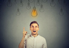 Happy young man pointing at light bulb has a solution Stock Images
