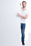 Happy young man points finger on a blank banner. Happy young man points finger on a blank banner - isolated on white Stock Photos