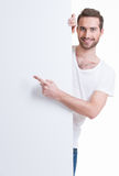 Happy young man points finger on a blank banner. Happy young man points finger on a blank banner - isolated on white Royalty Free Stock Photography