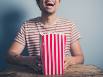 Happy young man with popcorn stock image