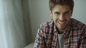 Happy young man. Portrait of handsome young man in casual shirt keeping arms crossed and smiling