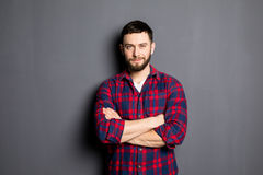 Happy young man. Portrait of handsome young man in casual shirt keeping arms crossed and smiling Stock Photos