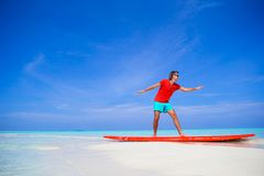 Happy young man practicing surfing position on. Strong young surf man runing at the beach with a surfboard Stock Image