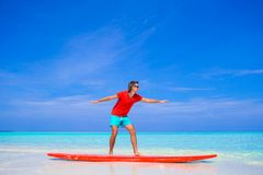 Happy young man practicing surfing position on Royalty Free Stock Photo