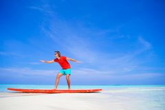 Happy young man practicing surfing position on. Strong young surf man runing at the beach with a surfboard Royalty Free Stock Photo