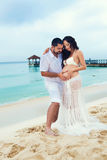 Happy young man and pregnant woman on the sea coast. Beautiful couple in love. Royalty Free Stock Photo
