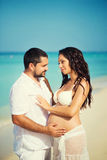 Happy young man and pregnant woman on the sea coast Stock Image