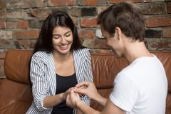Happy young man propose to his girlfriend sitting on sofa stock images