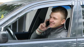 Happy young man pulls over on the road to talk on his cell phone. Businessman in car speaking on the smartphone stock video