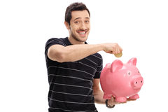 Happy young man putting a coin into a piggybank Stock Photography