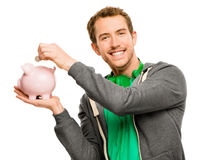 Happy young man putting money in piggy bank isolated on white Royalty Free Stock Images