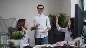 Happy young man putting pencil on the table and smiling women giving him five. Happy young man putting pencil on the table and smiling two women giving him five stock footage