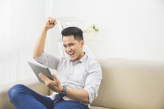 Happy young man raise his hand. success. Happy excited young man with tablet raised his arm at home sitting on a couch Royalty Free Stock Photo
