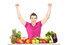Happy young man raising hands and sitting behind a pile of fruit Royalty Free Stock Photos