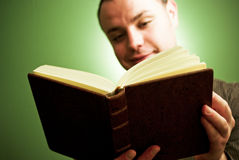 Happy young man reading book. Happy young adult male reading book Royalty Free Stock Image