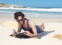 Happy young man reading book at the beach Stock Photo