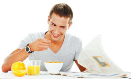 Happy young man reading newspaper Royalty Free Stock Photography