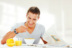 Happy young man reading newspaper Stock Image