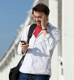 Happy young man reading text message on cell phone Royalty Free Stock Images