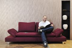 Happy young man realxing in modern living room Stock Photography