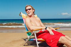Happy young man relaxing on the beach Stock Photography