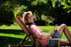 Happy young man relaxing on chair outdoors with digital tablet. Portrait of happy young african man relaxing on chair outdoors with a digital tablet on a summer stock photo