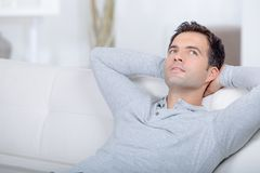 Happy young man relaxing in sofa in living room royalty free stock photography