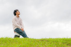 Happy young man rest on the grass field Stock Photography