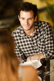 Happy young man in a restaurant. Happy young men smiling at his girlfriend in a restaurant Stock Photo