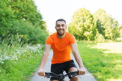 Happy young man riding bicycle outdoors. Fitness, sport, people and healthy lifestyle concept - happy young man riding bicycle outdoors Royalty Free Stock Images