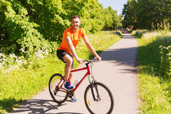 Happy young man riding bicycle outdoors Stock Photos