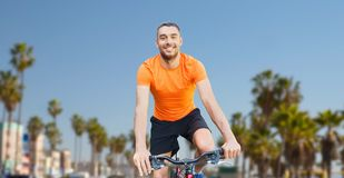 Happy young man riding bicycle over venice beach. Fitness, sport and healthy lifestyle concept - happy young man riding bicycle over venice beach background in Stock Photography