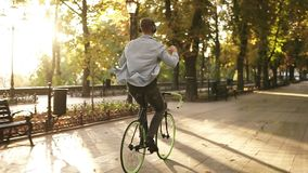 Happy young man riding bike in the park and listens to the music in black headphones. Man with outstretched hands stock video footage