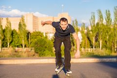 Happy young man rollerblading in city park at sunset. Outdoor, recreation, lifestyle, rollerblading royalty free stock photo
