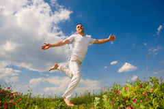 Happy young man is running in a field. Against the backdrop of blue sky Stock Photography