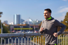 Happy young man running over city bridge. Fitness, sport, people and lifestyle concept - happy young man running over city bridge Royalty Free Stock Photography