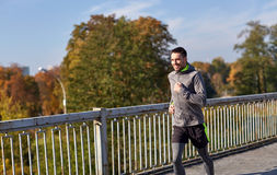 Happy young man running over city bridge. Fitness, sport, people and lifestyle concept - happy young man running over city bridge Royalty Free Stock Photos