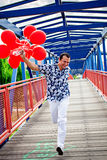 Happy young man running with red balloons Royalty Free Stock Photography