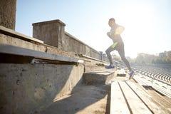 Happy young man running upstairs on stadium Stock Photos