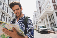 Happy young man searching place of destination. Active male tourist is reading map of city with aspiration. He is standing and smiling Stock Image