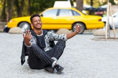 Happy young man seated down on pavement road with crossed legs,  on a yellow blurred taxi background. royalty free stock photography