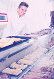 Happy young man seller working at meat market Royalty Free Stock Photography