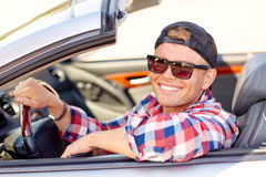 Happy young man in shades driving convertible car Stock Image